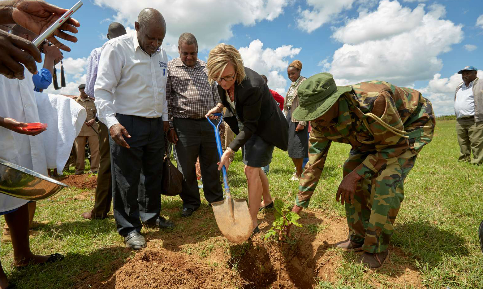 A Caucasian woman, WDF's Head of Programmes Hanne Strandgaard, digging a hole in the ground for a tree. She is surrounded by African men.